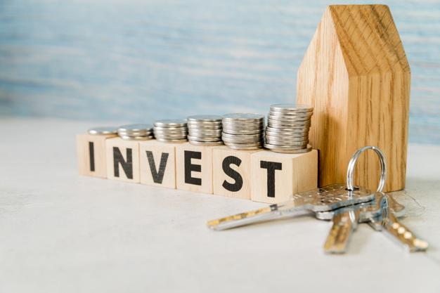 la-pila-di-monete-sopra-investe-i-blocchi-di-legno-vicino-al-modello-della-casa-con-le-chiavi-d-argento-sulla-superficie-di-bianco_23-2148038693